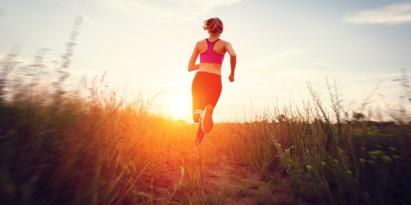 Young woman running on a rural road at sunset in summer forest. Lifestyle sports background